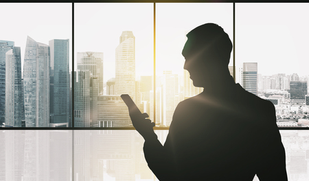 silueta hombre: business and people concept - silhouette of businessman with smartphone over office window and singapore city skyscrapers background and sun light Foto de archivo