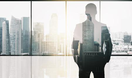 ビジネスや人々 のコンセプト - 事務所ウィンドウ、シンガポール市高層ビル背景と太陽光の二重露光効果にビジネスマンのシルエット