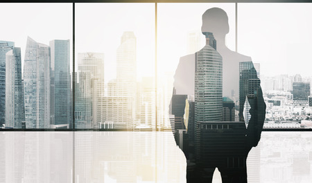 business and people concept - silhouette of businessman over office window and singapore city skyscrapers background and sun light double exposure effect Imagens