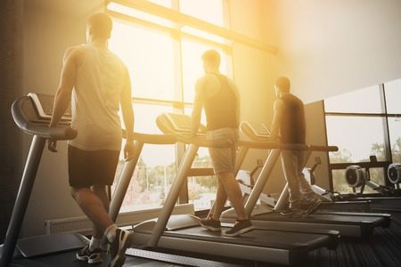 men exercising: sport, fitness, lifestyle, technology and people concept - men exercising on treadmill in gym Stock Photo