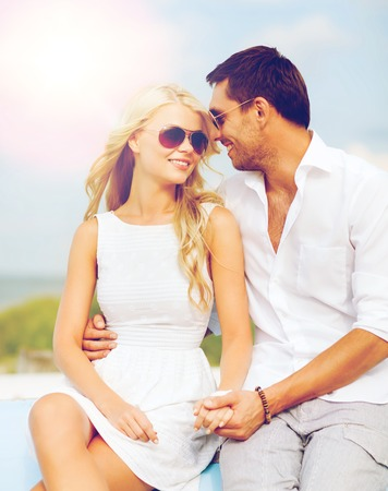 couple dating: summer holidays and dating concept - couple in shades at seaside