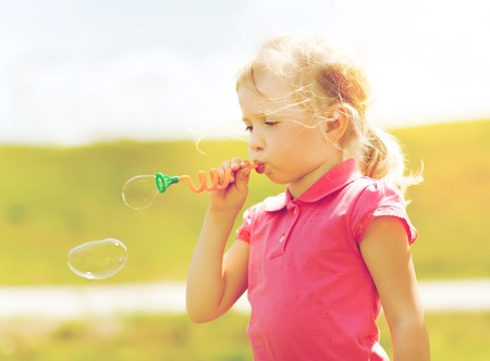 children clothing: summer, childhood, leisure and people concept - little girl blowing soap bubbles outdoors Stock Photo