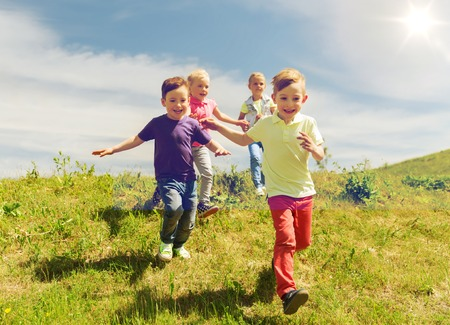 summer, childhood, leisure and people concept - group of happy kids playing tag game and running on green field outdoors Banco de Imagens