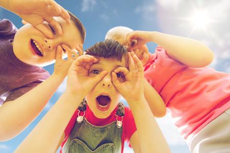 여름, 어린 시절, 레저 사람들 개념 - 행복한 아이들이 재미와 야외 얼굴을 만드는 그룹 스톡 콘텐츠
