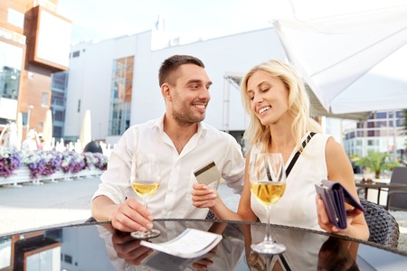 date, people, relations and finances concept - happy couple with wallet, credit card and wine glasses paying bill at restaurant Stock Photo