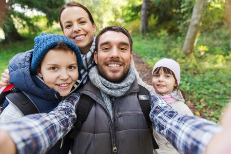 viaje familia: tecnología, viajes, turismo, caminata y concepto de la gente - familia feliz con mochilas teniendo autofoto y senderismo