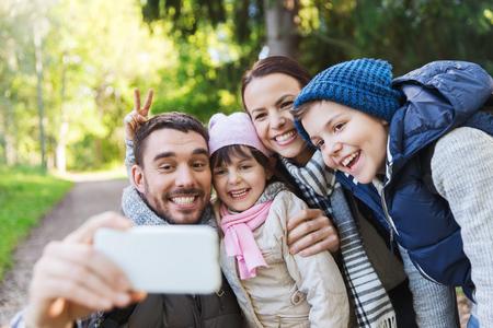 viaje familia: tecnología, viajes, turismo, caminata y concepto de la gente - familia feliz con mochilas que toman autofoto por teléfono inteligente y senderismo