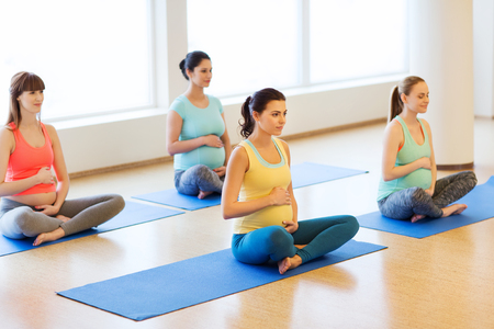 pregnancy yoga: pregnancy, sport, fitness, people and healthy lifestyle concept - group of happy pregnant women exercising yoga in lotus pose in gym Stock Photo