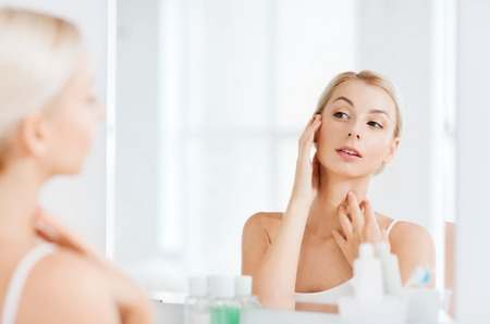 daily room: beauty, hygiene, morning and people concept - young woman looking to mirror at home bathroom