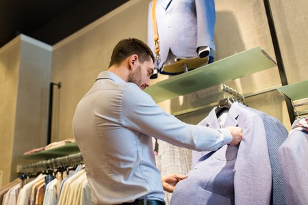 formal dressing: sale, shopping, fashion, style and people concept - close up of man choosing jacket at clothing store