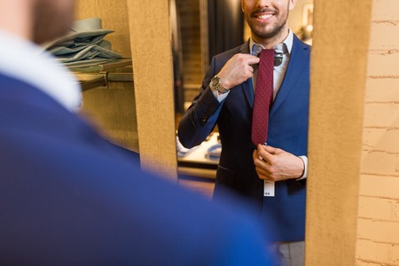 sale, shopping, fashion, style and people concept - elegant young man choosing and trying tie on and looking to mirror in mall or clothing store