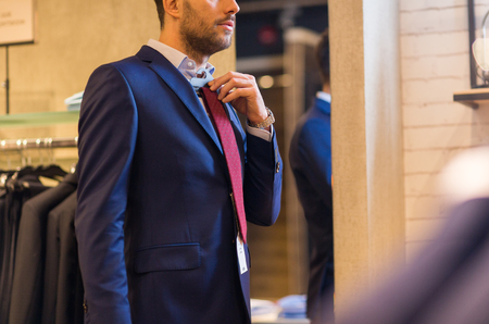 formal dressing: sale, shopping, fashion, style and people concept - elegant young man choosing and trying tie on at clothing store Stock Photo