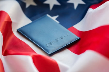 citizenship: citizenship, patriotism and nationalism concept - close up of american flag and passport