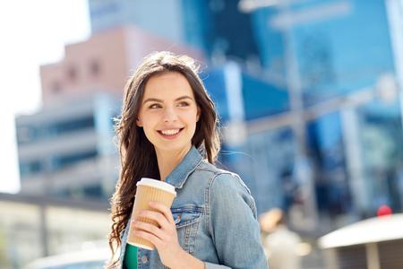 drankjes en mensen concept - happy jonge vrouw of tiener meisje drinken koffie uit kartonnen beker op stadsstraat