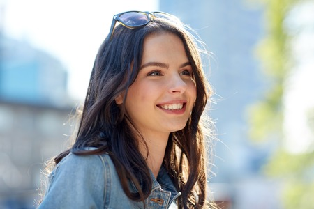 women and people concept - happy smiling young woman on summer city street Stock Photo