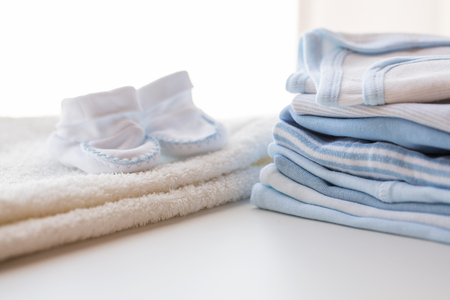 bootees: clothing, babyhood, motherhood and object concept - close up of white baby bootees, towel and pile of clothes for newborn boy Stock Photo