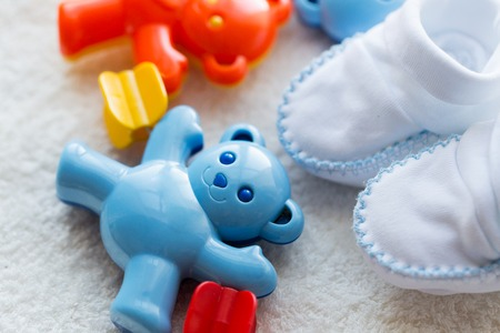 bootees: babyhood, childhood, toys, clothing and object concept - close up of baby rattle and bootees for newborn boy on towel