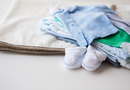 bootees: clothing, babyhood, motherhood and object concept - close up of baby bootees and pile of clothes for newborn boy