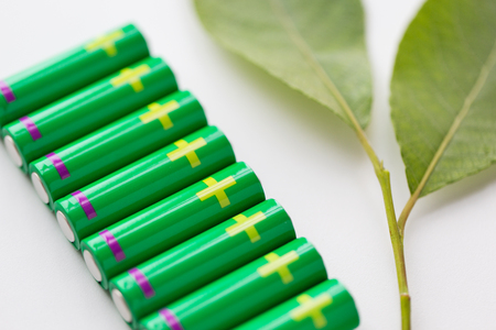 power concept: recycling, energy, power, environment and ecology concept - close up of green alkaline batteries and leaf Stock Photo
