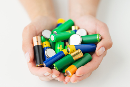 heap up: recycling, energy, power, environment and ecology concept - close up of hands holding alkaline batteries heap