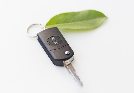 hybrid car: conservation, environment, transport and ecology concept - close up of car key and green leaf trinket