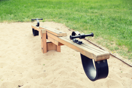 childhood, equipment and object concept - close up of swing or teeterboard on playground outdoors Stock Photo