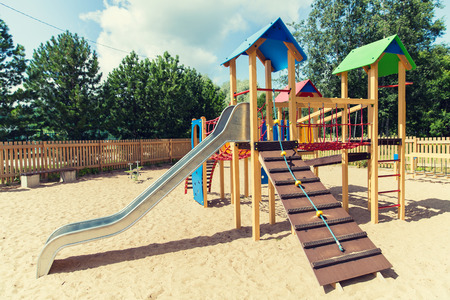 climbing frame: childhood, equipment and object concept - climbing frame with slide on playground outdoors at summer