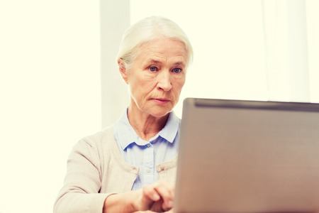 computer age: technology, age and people concept - senior woman with laptop computer at home