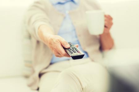 señora mayor: la tecnología, la televisión, la edad y el concepto de la gente - cerca de una mujer mayor mirando televisión, bebiendo té y cambiar los canales con control remoto en casa