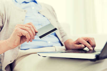 emoney: technology, age and people concept - close up of senior woman with laptop compute and credit or bank card r at home