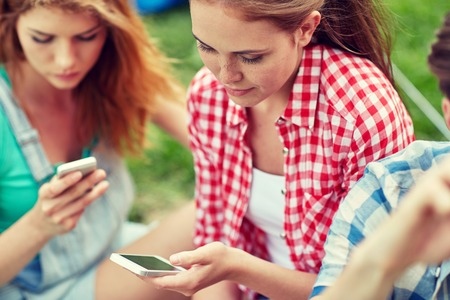 smartphone addiction: internet addiction, technology and people concept - group of friends with smartphone at camping