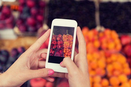 technology market: sale, shopping, food, technology and people concept - close up of hands with smartphone taking picture of fruits at street market Stock Photo