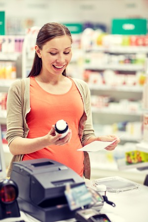prescription medicine: pregnancy, medicine, pharmaceutics, health care and people concept - happy pregnant woman with medication and prescription paper at pharmacy cash register