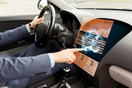 finger shape: transport, business, modern technology and people concept - close up of man driving car and pointing finger to chart and low poly shape on board computer screen Stock Photo
