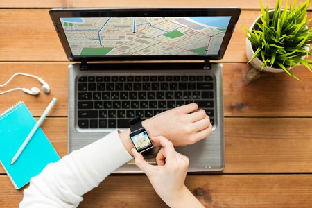 gprs: navigation, location, business, people and technology concept - close up of woman with smart watch and laptop computer on wooden table with gps navigator map on screens