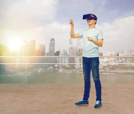 entertainment background: 3d technology, virtual reality, entertainment, cyberspace and people concept - man with virtual reality headset or 3d glasses playing game and touching something over city skyscrapers background