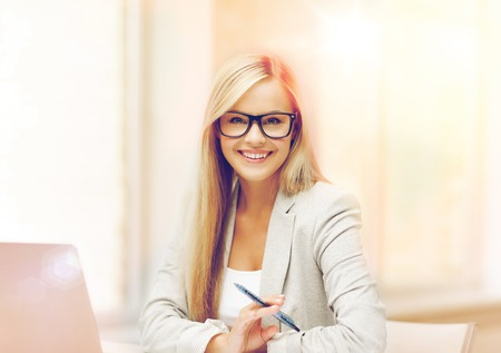 indoor picture of smiling woman with laptop and pen