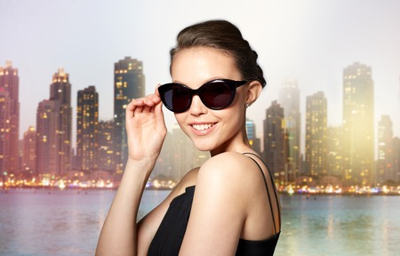 eyewear fashion: accessories, eyewear, fashion, people and luxury concept - beautiful young woman in elegant black sunglasses over dubai night city lights street background