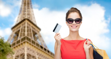 people, finances, tourism, travel and sale concept - young happy woman with shopping bags and credit card over paris eiffel tower background