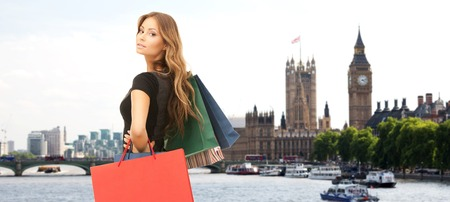 travel woman: people, holidays, tourism, travel and sale concept - young happy woman with shopping bags over london city background