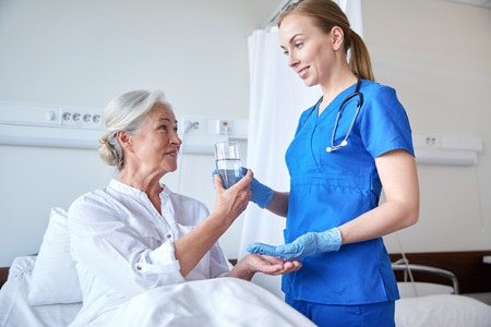 doctor giving pills: medicine, age, health care and people concept - nurse giving medication and glass of water to senior woman at hospital ward