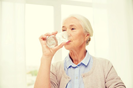 home health care: age, health care and people concept - happy senior woman with glass of water at home
