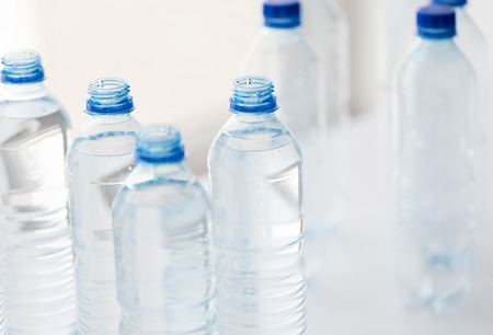 food storage: recycling, healthy eating and food storage concept - close up of plastic bottles with pure drinking water on table