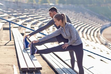 fitness, sport, l'exercice et le concept de style de vie - quelques étirements jambe sur les stands de stade