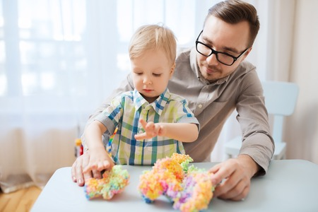 family, childhood, creativity, activity and people concept - happy father and little son playing with ball clay at home Stock Photo