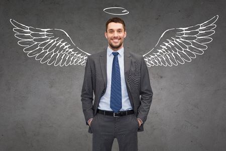 bedrijfsleven, angel investor, veiligheid, beveiliging en mensen concept - lachende jonge zakenman met vleugels en nimbus tekening over grijze concrete achtergrond