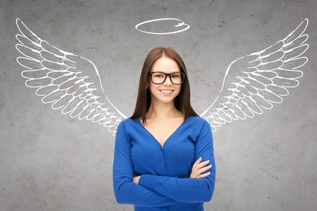 bedrijfsleven, angel investor, veiligheid, beveiliging en mensen concept - lachende jonge zakenvrouw met vleugels en nimbus tekening over grijze concrete achtergrond Stockfoto