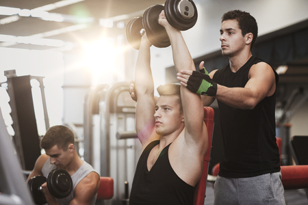 powerlifting: sport, fitness, lifestyle, powerlifting and people concept - group of men with dumbbells and personal trainer flexing muscles in gym Stock Photo