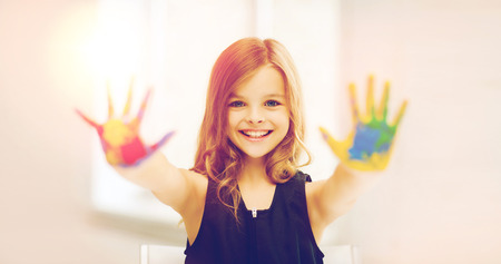 painted hands: education, school, art and painitng concept - little student girl showing painted hands at school