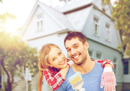 repair, building and home concept - smiling couple covered with paint with paint brush Stock Photo